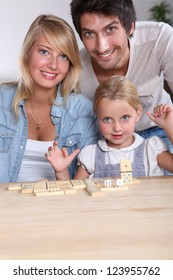 Parents and daughter playing dominoes