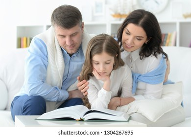 parents and daughter reading big book in room