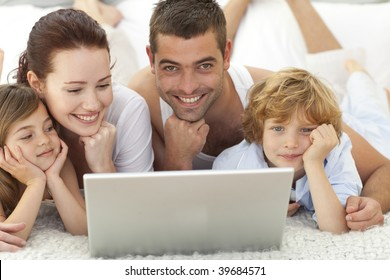 Parents and daughter and son in bed using a laptop
