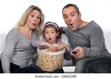 Parents with daughter watching TV and eating popcorn