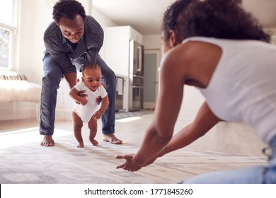 Parents Encouraging Smiling Baby Daughter To Take First Steps And Walk At Home