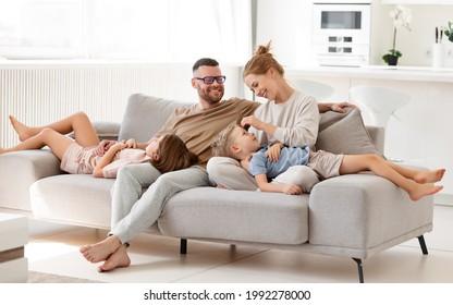 Eltern, die Liebe zu Kindern ausdrücken. Schöne glückliche Familie von vier, Mutter, Vater und zwei süße Kinder verbringen Zeit zusammen zu Hause, umarmen und entspannen auf Sofa im Wohnzimmer