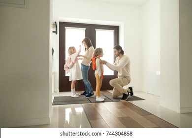 Parents get children ready for school standing at hallway, mother and father helping little preschool kids boy girl put backpacks on at home hall, mom with dad dressing son daughter in the morning