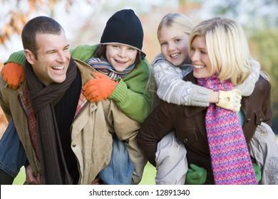 Parents giving children piggyback ride through autumn trees