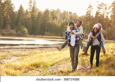 Parents Giving Children Piggyback Ride On Walk By Lake - Shutterstock ID 388719088