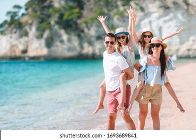 Parents giving children piggyback rides on the beach