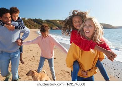 Parents Giving Children Piggybacks As They Walk Along Winter Beach Together