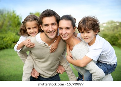 Parents giving piggyback ride to children