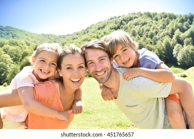 Parents giving piggyback ride to kids in mountains