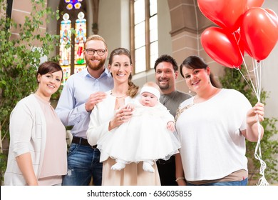 Parents and godparents pose for a photo after the christening with the baby and red balloons