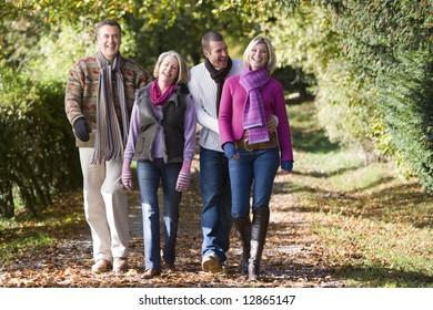 Parents and grown up children walking through autumn woods