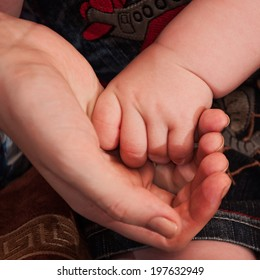 Parent's hand holding his baby's hand