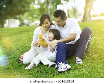 parents having fun with their daughter in the park