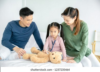 Parents having fun with their little daughter on bed playing doctor and curing Teddy bear indoors.  Medicine and health care concept.