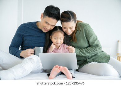 Parents having fun with their little daughter on bed with tablet. Family spending time at the holiday , happy family concept.