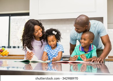 Parents helping children doing homework in the kitchen