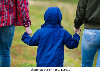 parents hold the baby by the hands, rear view. Father and mother hold the hands of his son in a blue jacket with a hood and walk along a country road. Close-up