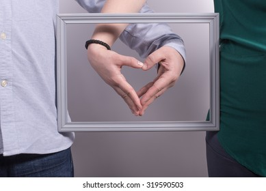 Parents holding hands in a heart shape on frame