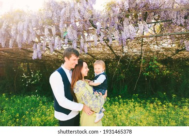 Parents holding their baby boy in their arms under a blooming wysteria tree