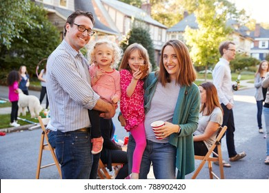 Parents holding young kids smile to camera at a block party
