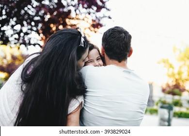 parents hug their beloved daughter