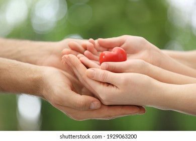 Parents and kid holding red heart in hands outdoors, closeup. Family day
