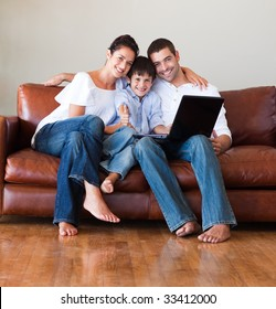 Parents and kid using a laptop with thumbs up on a couch