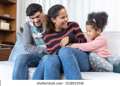 Parents and kids having fun tickling sitting together on sofa in living room at home, Happy family time concept