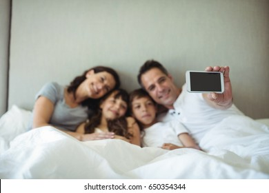 Parents and kids taking a selfie on bed at home