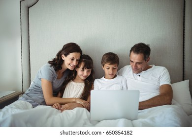 Parents and kids using laptop in bed at home