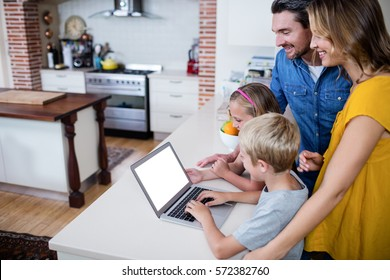 Parents and kids using laptop in kitchen at home