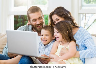Parents and kids using laptop in living room at home
