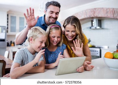 Parents and kids waving hands while using digital tablet for video chat in kitchen