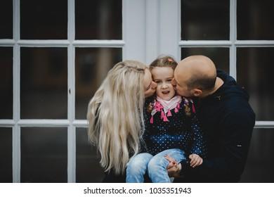Parents kiss little girl tender standing before the doors outside
