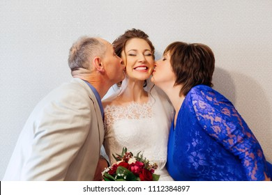 Parents kiss their smiling daughter on her wedding day.