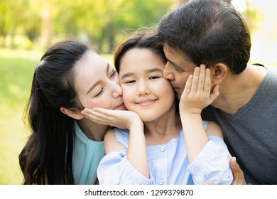 parents kissing their daughter. Family Holiday Vacation