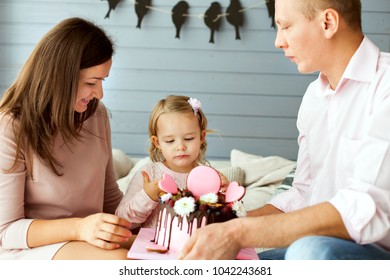 Parents with a little daughter. Girl is trying the cake with her finger