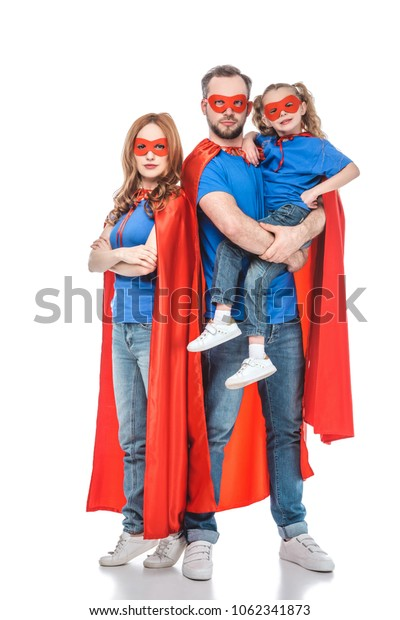parents with little daughter pretending to be superheroes and looking at camera isolated on white