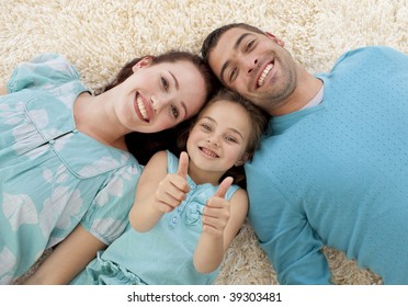 Parents and little girl lying on floor with heads together and thumbs up