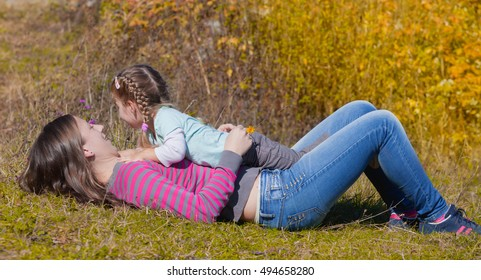 Parents and little girl playing and having fun outdoors during the fall season
