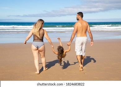 Parents and little kid wearing swimsuits, walking on golden sand to water. Girl holding parents hands, hanging and throwing legs up. Rear view. Family outdoor activities concept