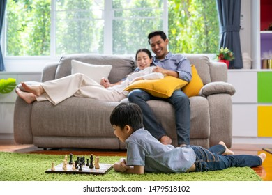 Parents looking at their children happiness playing chess in the living room