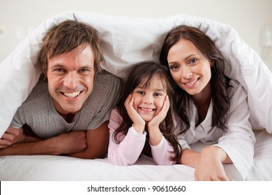 Parents lying under a duvet with their daughter in their bedroom