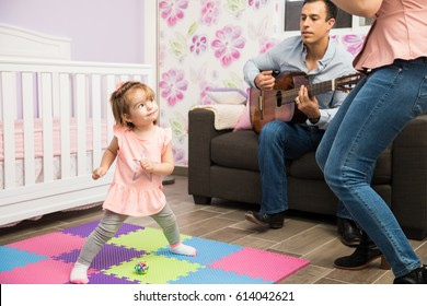 Parents making her cute child show her dance moves with some music played by her dad with an acoustic guitar