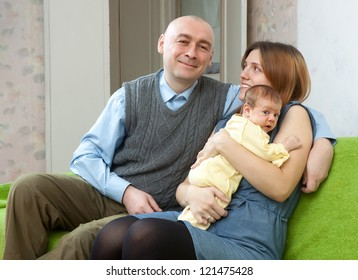 parents with newborn baby of sofa in home interior