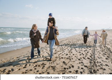 parents piggybacking son while grandparents holding hands with granddaughter, walking together on seashore
