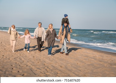 parents piggybacking son while grandparents holding hands with granddaughter, walking together at seaside