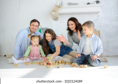 Parents play cubes with children. Joint leisure. Three children of different ages are building something with interest. Everyone has a great mood.