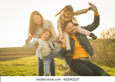 Parents play with his daughters in the park. Daughter sitting on father shoulders.