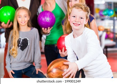 Parents playing with children together at bowling center
